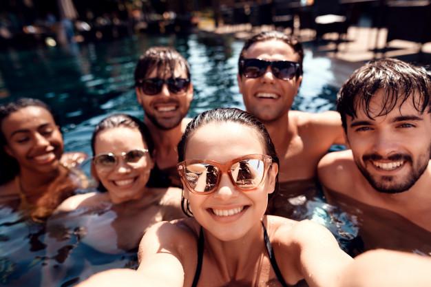 jovens amigos felizes fazem selfie na piscina